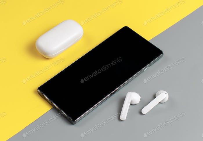 Smartphone und weiße kabellose Ohrhörer