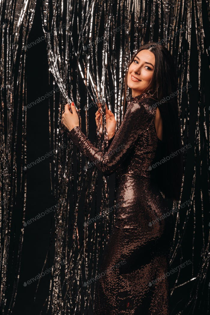 girl in a shiny dress on a silver background of New Year's rain