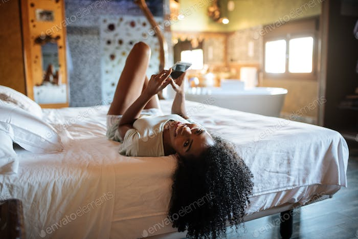 Woman on the bed with mobile phone