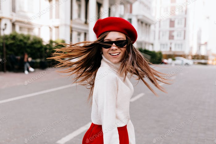 Outdoor portrait of cute woman  in french outfit with happy smile turn around in London