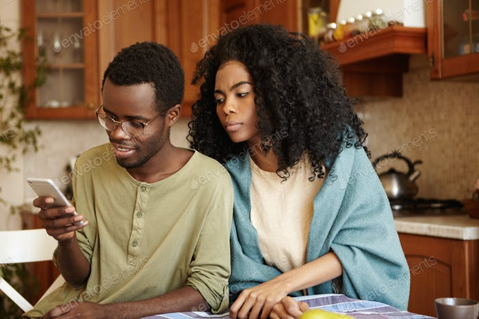 Suspicious black wife with Afro hairstyle trying to read message that her happy husband sending to s