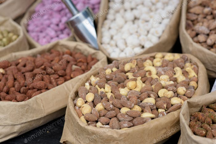 Almonds and pistachios with spices lie in paper bags on the counter.