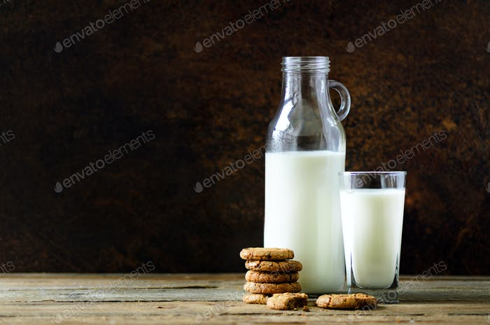 Chocolate chip cookies, bottle and glass of milk on wooden table, dark background. Sunny morning