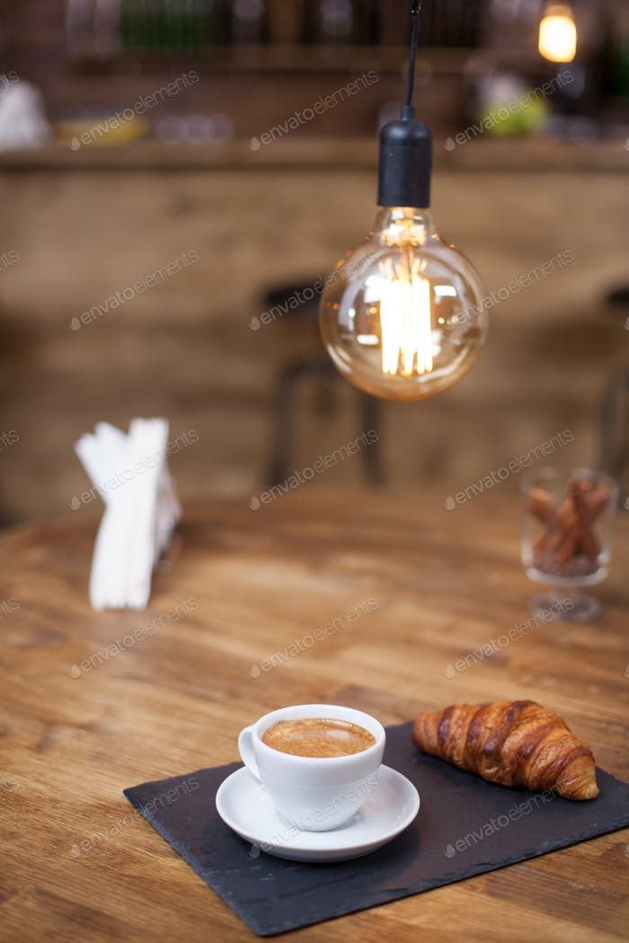 Fresh roasted coffee in a white coffee cup with tasty croissant on a vintage pub