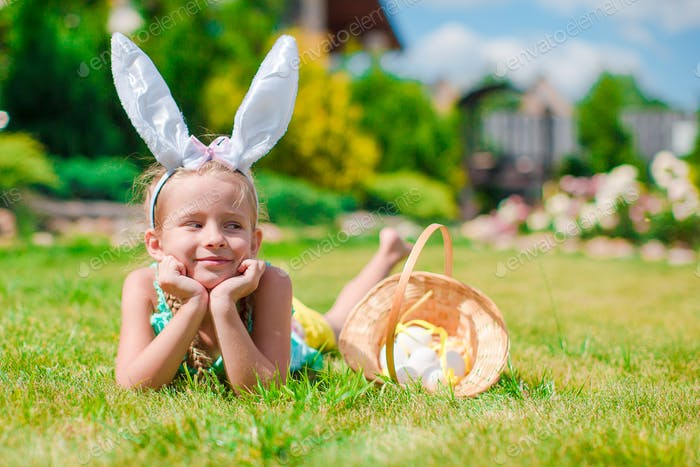 Adorable little girl wearing bunny ears and basket with Easter eggs