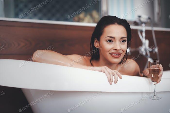 Portrait of woman in bathtub drinking champagne