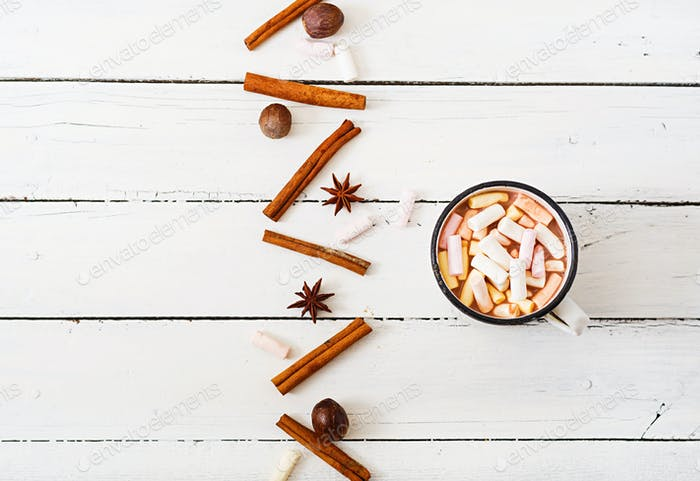 Cup of hot cocoa or chocolate with marshmallow on a light wooden background. Flat lay. Top view
