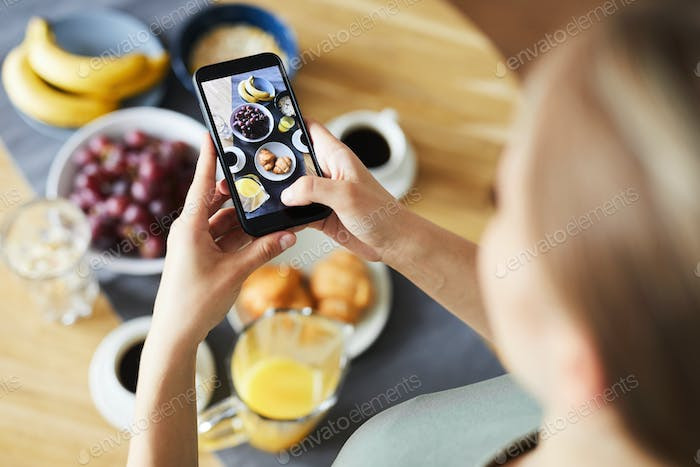 Contemporary girl with smartphone taking shot of her served table