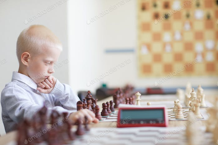 Serious schoolboy playing chess
