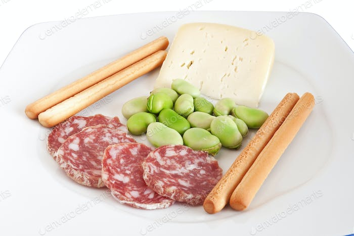 dish with fava beans, breadstick and salami slices