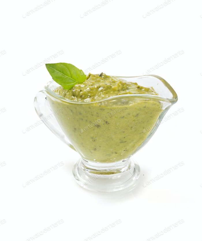 pesto sauce in gravy boat on white