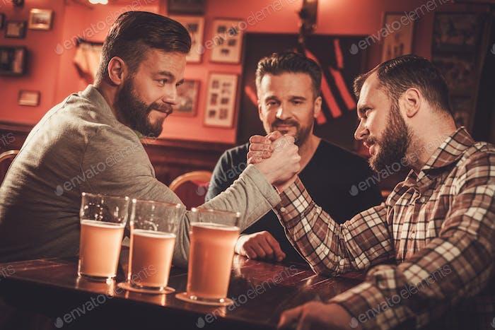 Fröhliche alte Freunde mit Arm Wrestling Herausforderung in einem Pub.