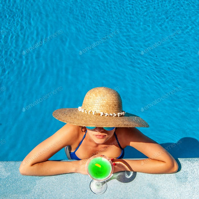Woman at poolside with cocktail