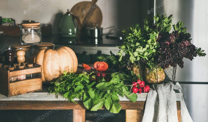 Variety of fresh vegetable ingredients on concrete kitchen counter