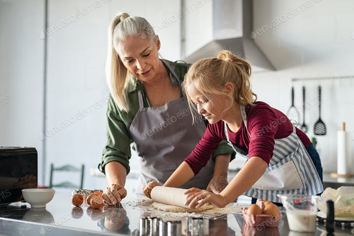 Little girl rolling dough with grandmother