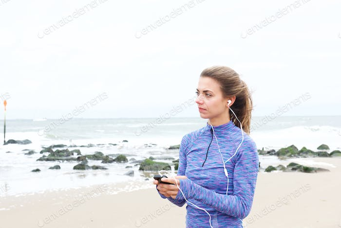 Beautiful woman standing on beach holding phone with earphones