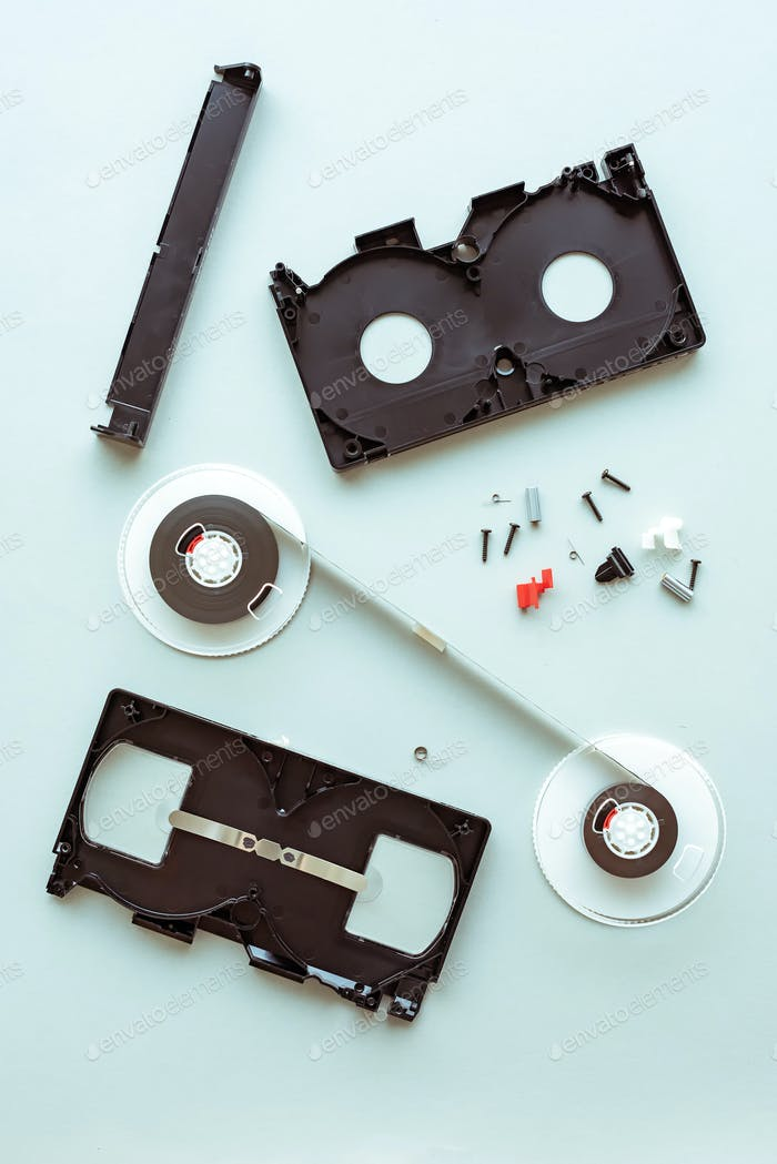 Flat lay vhs video cassette parts on pastel blue background