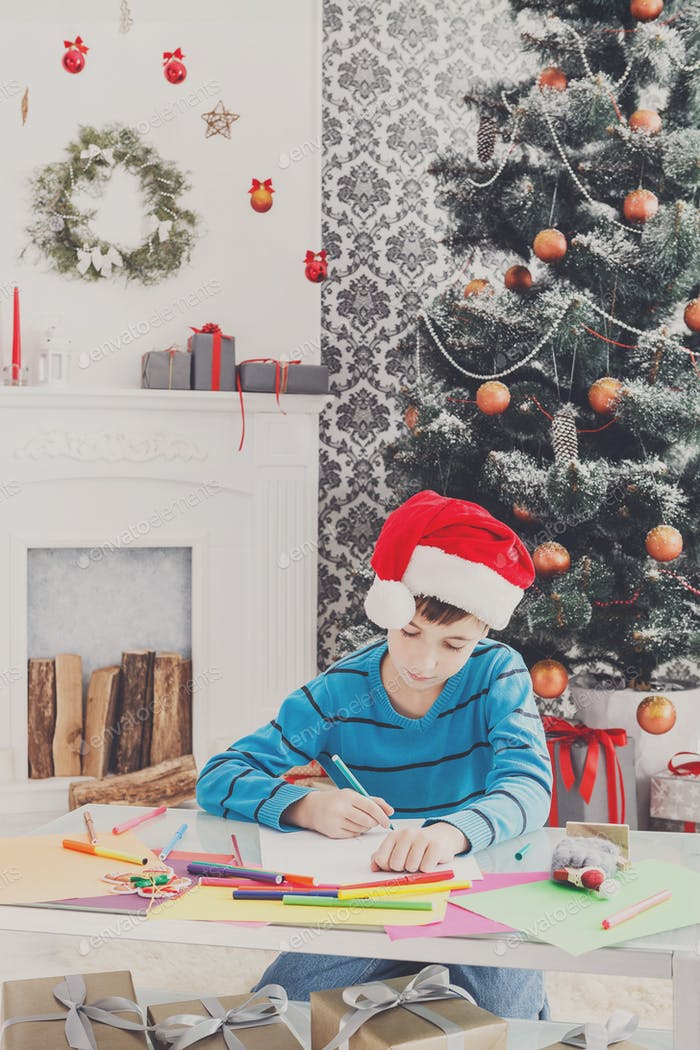 Cute boy writing letter to santa, wait for christmas
