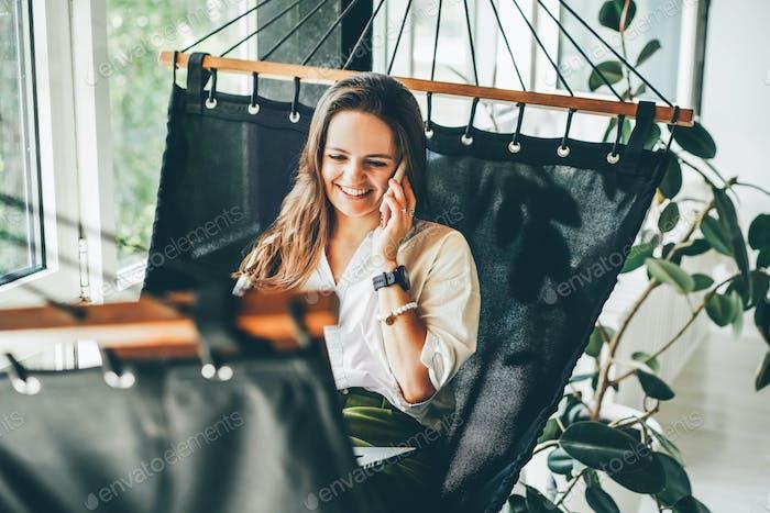 Businesswoman working on a hammock.