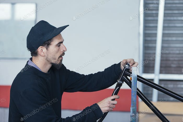 Side view of man constructing bicycle