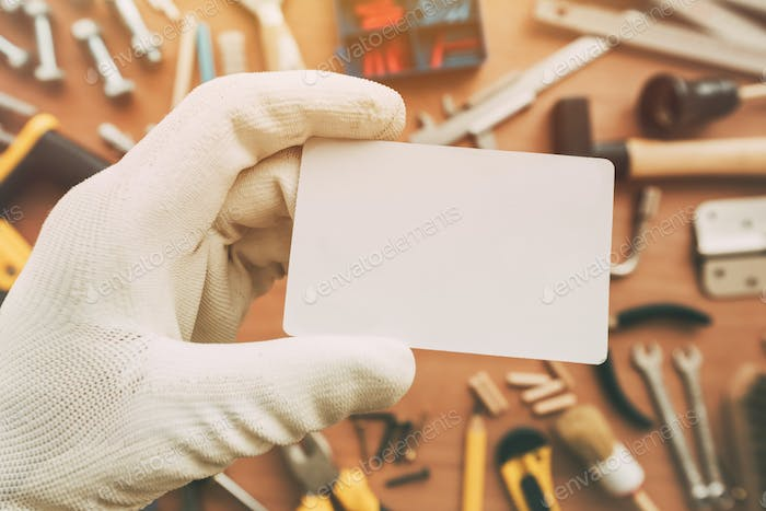 Worker holding blank business card as copy space