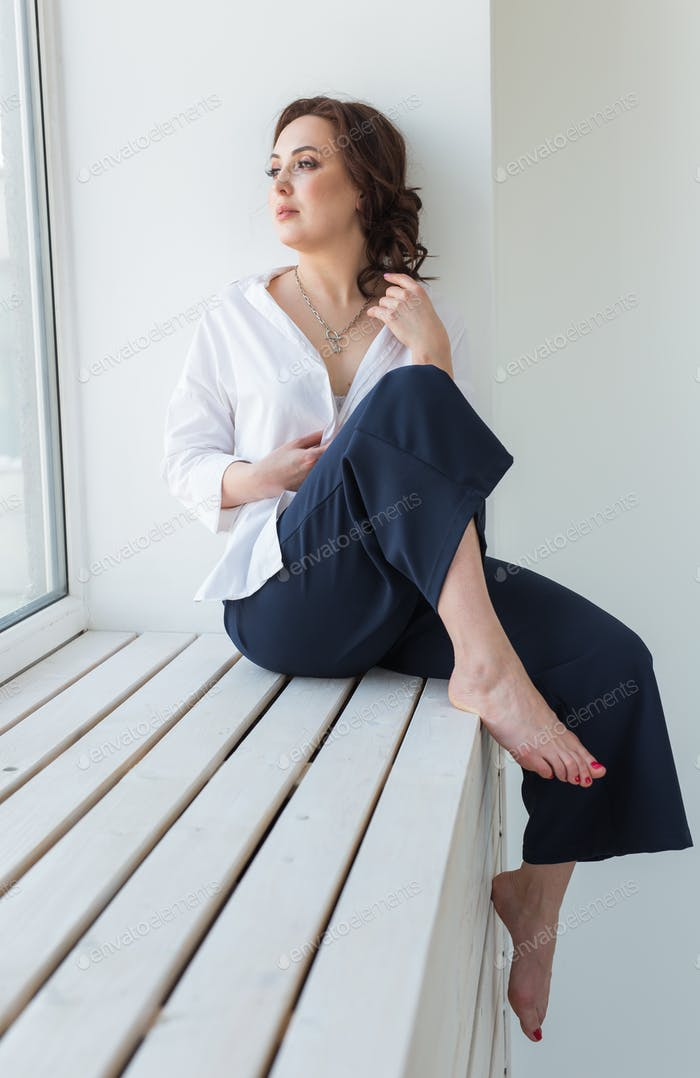 Close-up of fashion shoot of young brunette woman with elegant hairstyle in white studio. Trendy
