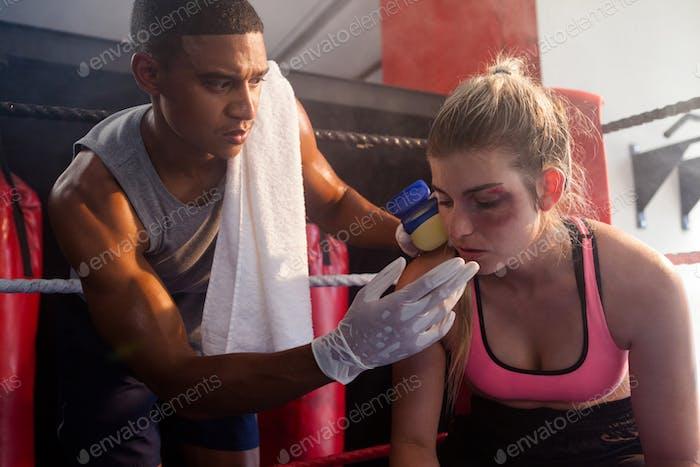 Trainer applying cream on woman face