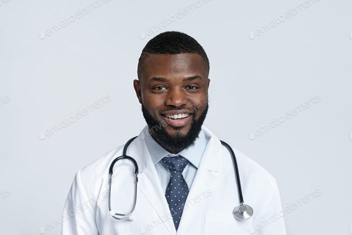 Portrait of cheerful black doctor with stethoscope on white background