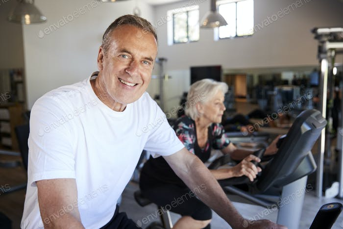 Portrait Of Active Senior Man Resting After Exercising On Cycling Machines In Gym