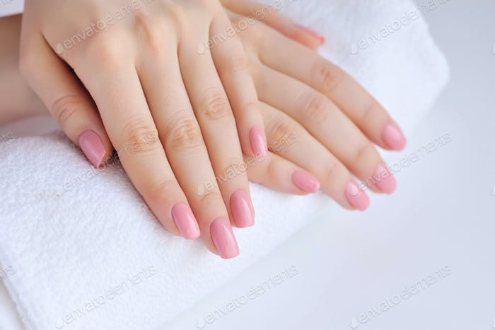 Hands of a woman with pink manicure are on a towel