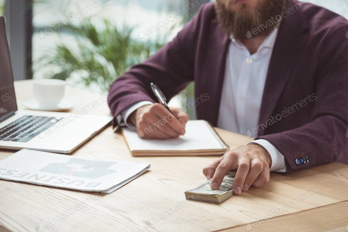 cropped view of businessman writing and holding dollar banknotes, salary concept
