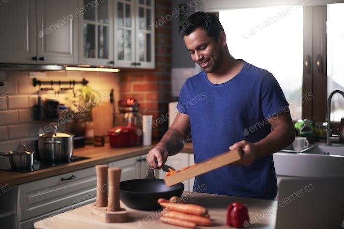 Happy man cooking in kitchen