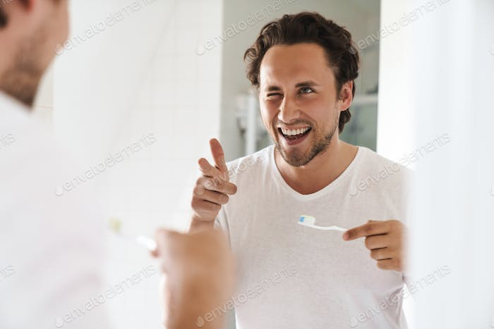 Attractive young man standing in front of the bathroom mirror