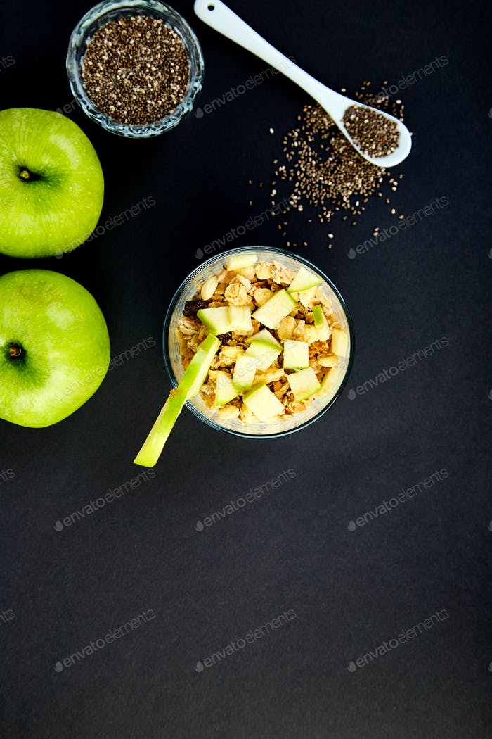 Healthy chia pudding with apples and granola in glass.