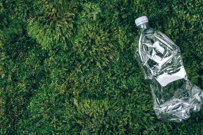 Plastic bottles on green moss background. Recycle plastic, waste pollution concept. Top view, copy