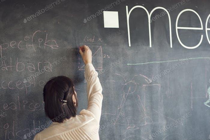 Rückansicht der kreativen Geschäftsfrau Schreiben auf Tafel im Büro