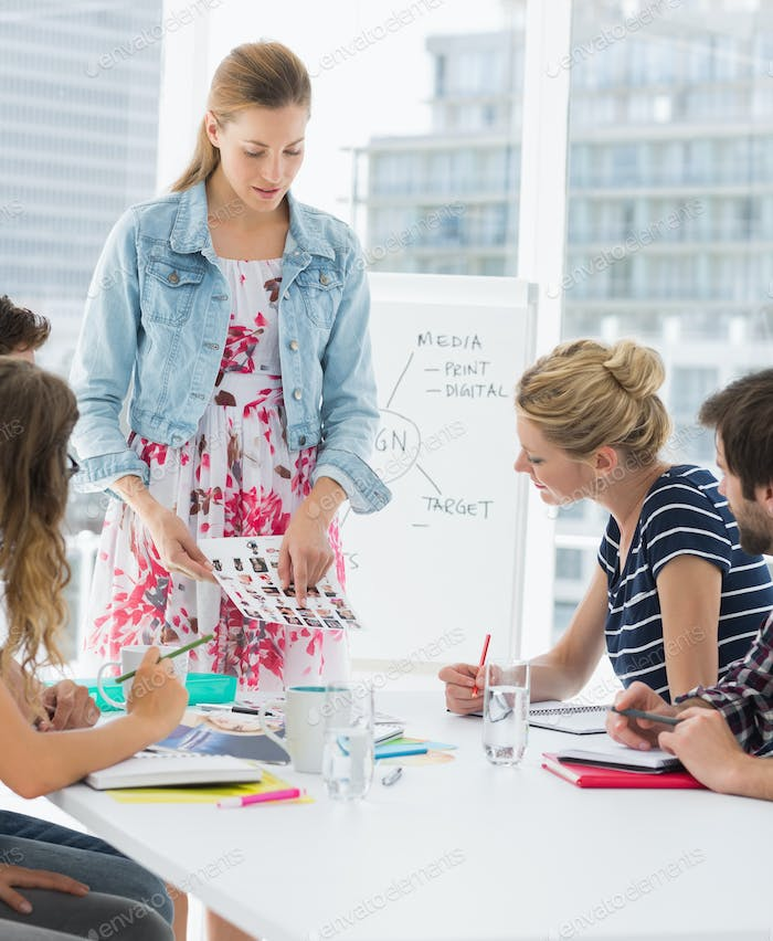 Young casual businesswoman presenting new project to partners