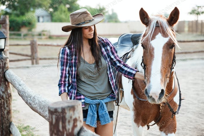 Woman cowgirl walking with her horse on ranch