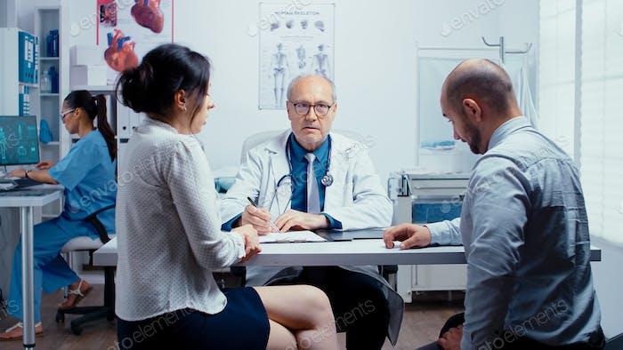 Junges Paar im Gespräch mit Seniorarzt