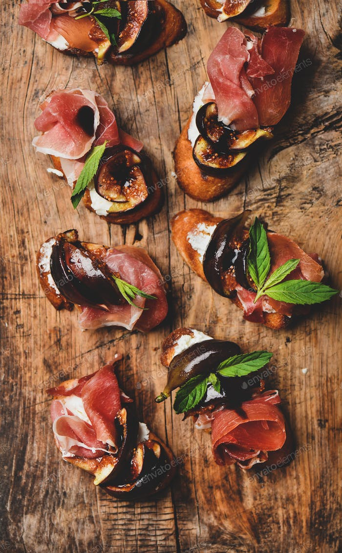 Crostini with prosciutto, goat cheese and grilled figs on board