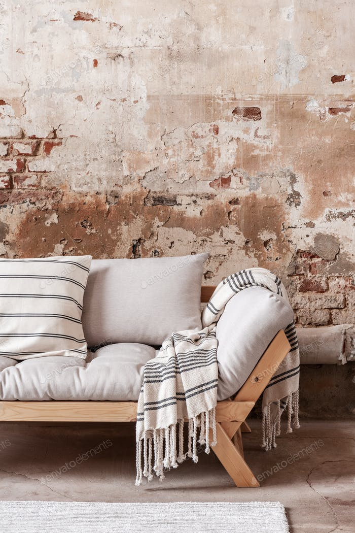 Patterned blanket and pillows on wooden grey couch against red b