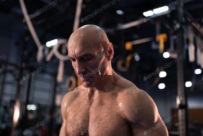 Sweaty elderly sportsman resting between exercises