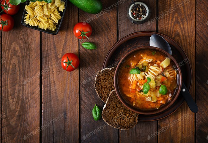 Minestrone, italian vegetable soup with pasta on wooden table. Top view