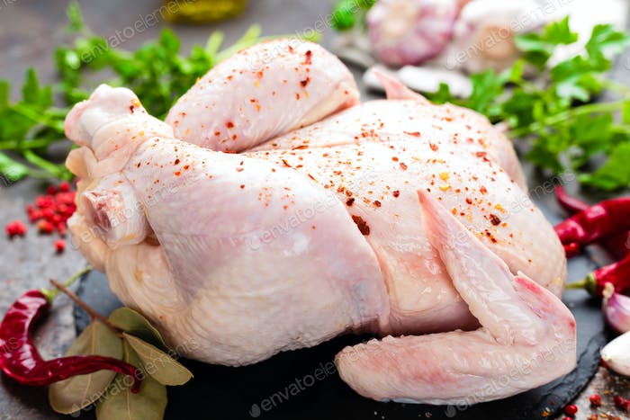 Raw chicken. Fresh whole chicken with ingredients for cooking