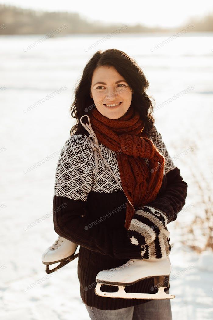 Mujer sonriente con un par de patines atados juntos sobre un hombro
