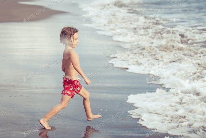 Portrait of little boy standing on the beach
