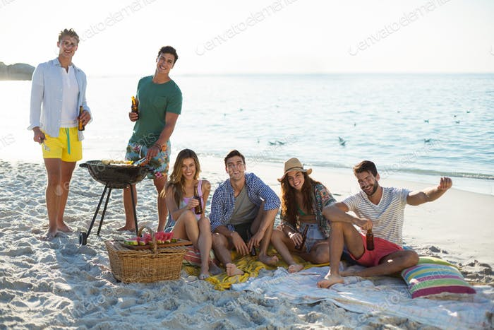 Lächelnde Freunde mit Drinks durch Grill am Strand