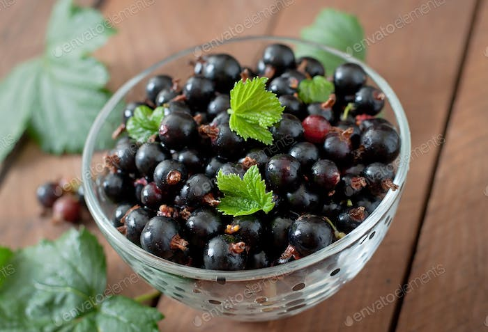 Black currants in a glass bowl on a wooden background