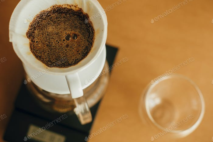Brewing aromatic fresh coffee in paper filter closeup in pour over on scale