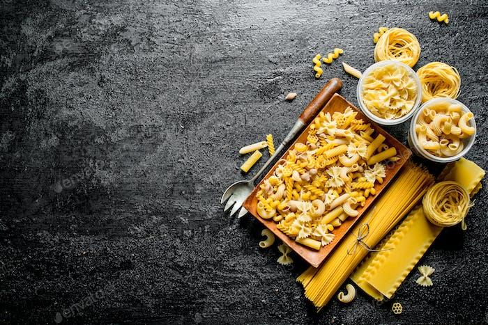 Sortiment verschiedener Arten von trockenen Nudeln auf einem Teller mit Schöpfkelle.